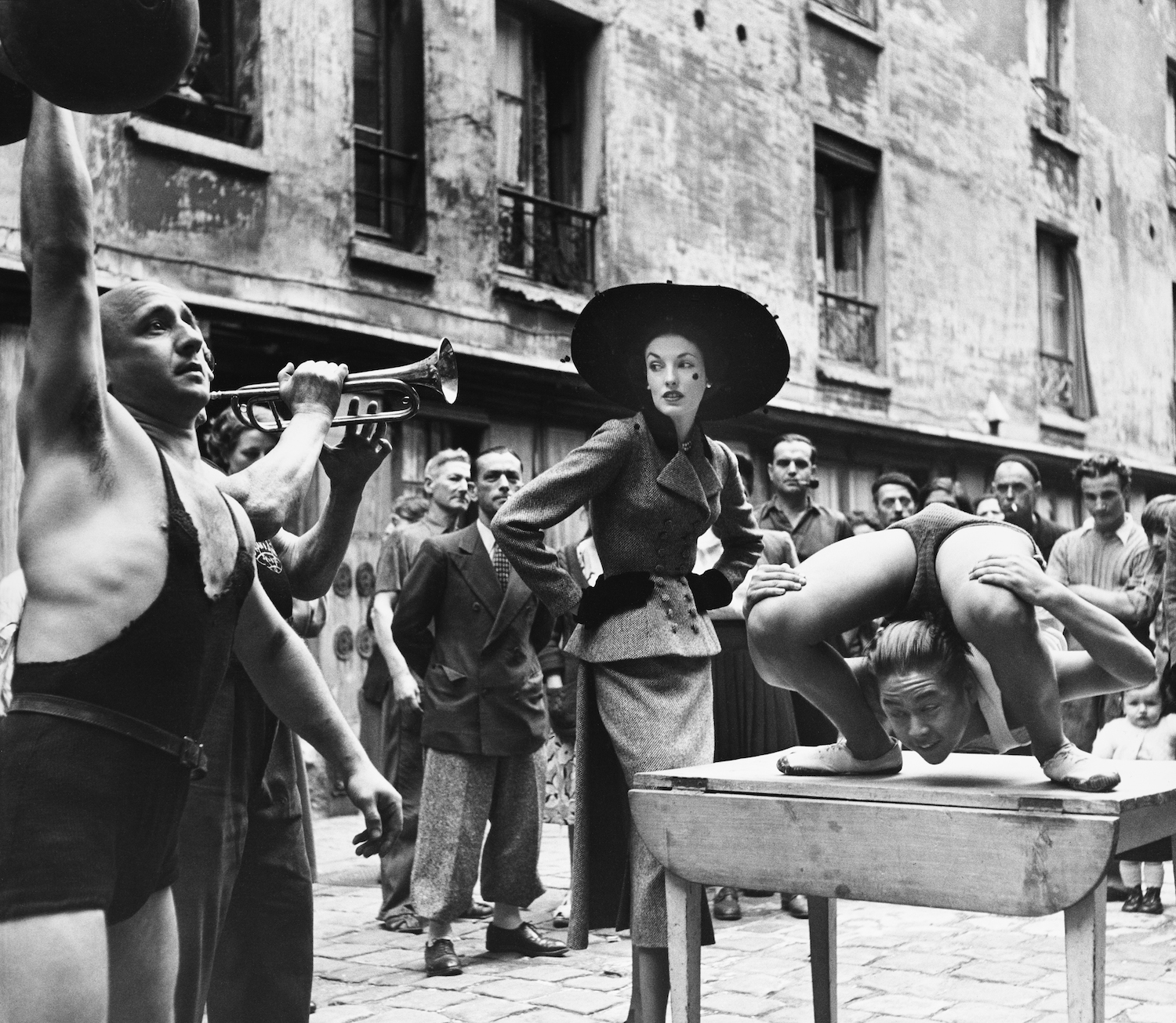 Richard Avedon (1923 – 2004) | Elise Daniels with street performers, suit by Balenciaga, Le Marais, Paris, 1948 | © The Richard Avedon Foundation | Balenciaga: Shaping Fashion at V&A; 27 May 2017 – 18 Feb 2018; vam.ac.uk/balenciaga